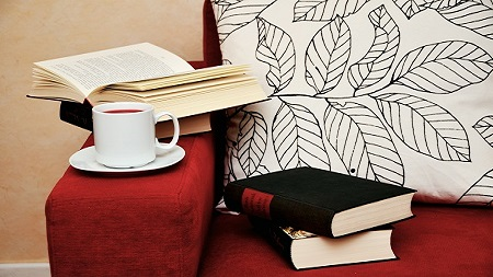 An armchair with books and tea