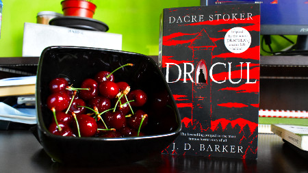 Dracul by Dacre Stoker and J.D.Barker next to a bowl of cherries